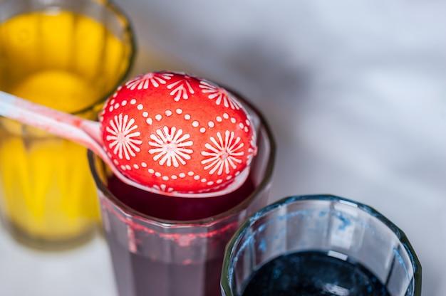 Процесс покраски пасхальных яиц пищевым красителем и растопленным воском.