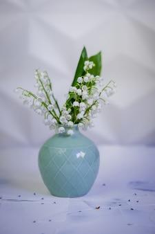 白い背景の上のセラミック花瓶の谷のユリの花。母の日グリーティングカード。