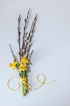 イースターの背景黄色の水仙と柳の枝の春の背景
