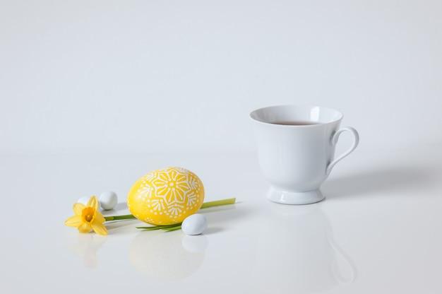 黄色の塗られた卵と白い背景の上の水仙の紅茶のカップ。春のコンセプトです。