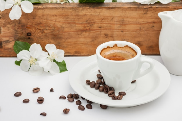 Утренний кофе с яблоней цветы на белом столе в саду.