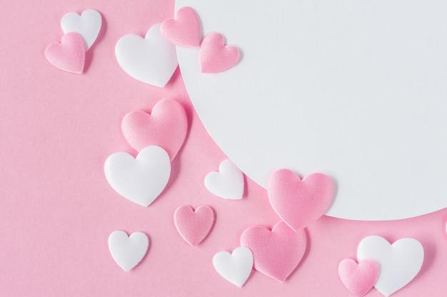 バレンタインデーのコンセプト。ピンクと白の心とテキスト用のスペースのグリーティングカード。上面図。平干し。閉じる。