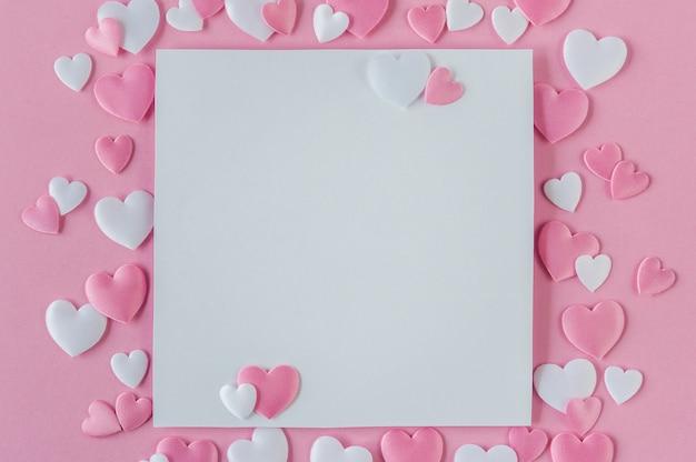 バレンタインデーのコンセプト。ピンクと白の心とピンクの背景上のテキストのためのスペースのグリーティングカード。上面図。平干し。閉じる。