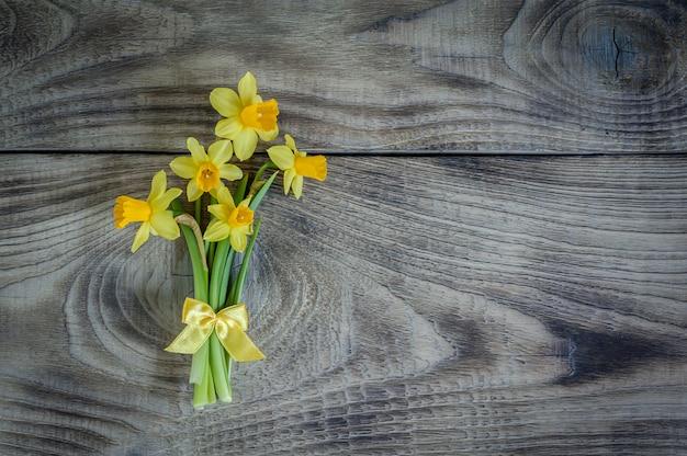 木製のテーブルに水仙の花束。グリーティングカードのレイアウト