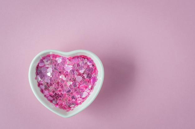 Блестки в миске в форме сердца, керамическая чашка на розовом