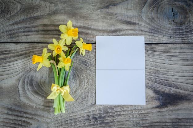 白いカードと木製のテーブルの上の水仙の花束。