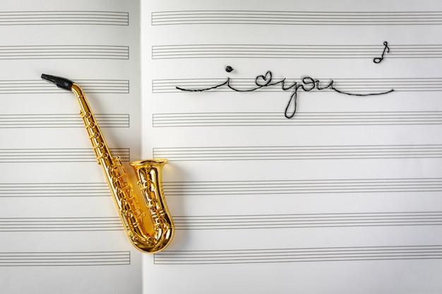 Саксофон на фоне музыкальной тетради со словами я тебя люблю