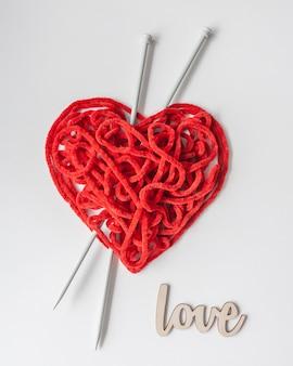 針と木製の看板の白い編み糸の赤い編み糸。ハート型。バレンタインデーの最小限のコンセプト。