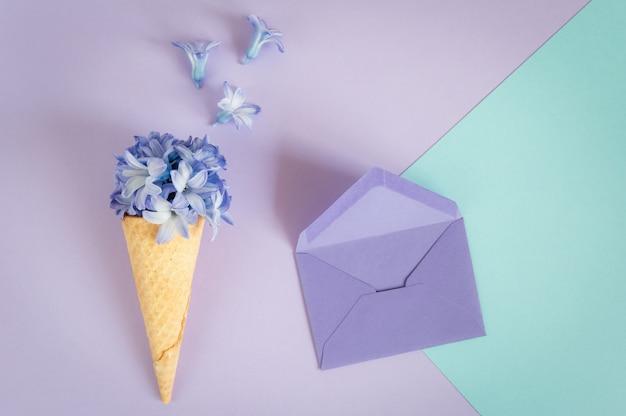 アイスクリームの角または紫色の背景に紫のヒヤシンスとコーン。