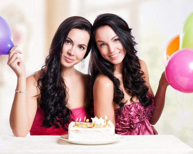 Две счастливые молодые женщины с тортом