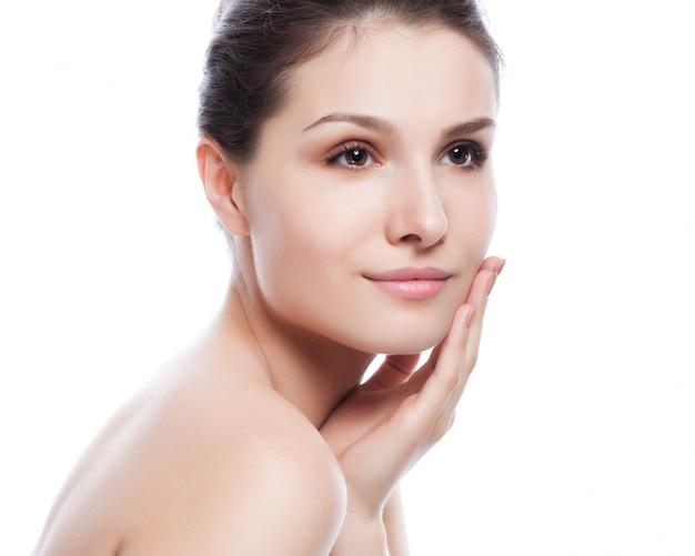 彼女の顔に触れる美しい若い女性。新鮮な健康的な肌。白で隔離