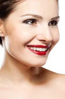 美しい女性の顔。完璧なこぼれるような笑顔。白人の若い女の子は肖像画を閉じます。赤い唇、肌、歯。白い背景に分離されました。
