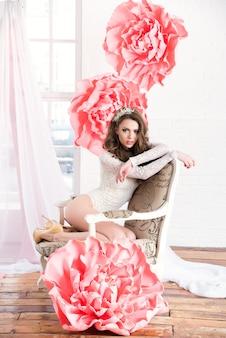窓際に座っている巨大なピンクの花と長いドレスの美しいセクシーな女の子