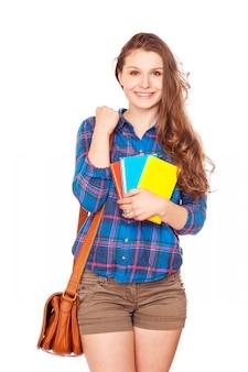 Счастливая молодая девушка студента держа книги, выпускника средней школы или колледжа, милый вскользь усмехаться подростка