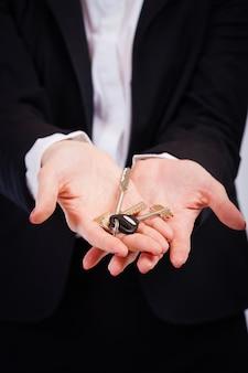 Бизнес женщина держит ключи на белом фоне