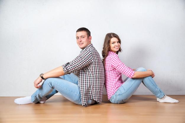 若いカップルの家の床でくつろいで裸足で背中合わせに空気を見上げる