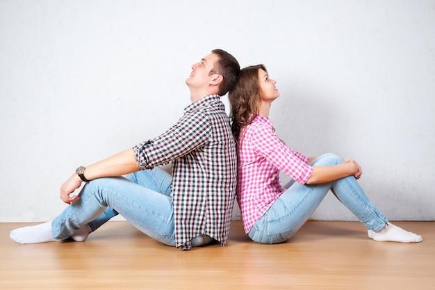 若いカップルの家の床でくつろいで裸足で背中合わせに見上げる