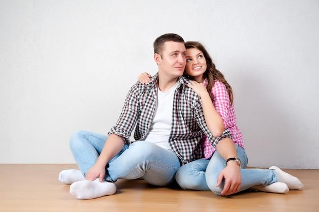 Красивая босая молодая пара в повседневных джинсах сидит прислонившись к белой стене на деревянном полу в гостиной, улыбаясь в камеру