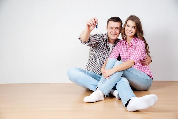 Ключ от их нового дома. счастливая молодая пара стоя рядом друг с другом и улыбаясь, удерживая ключ от дома