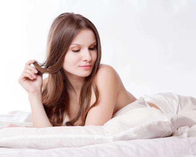 Красивая романтическая женщина / девушка брюнетка лежа на кровати в своей комнате дома
