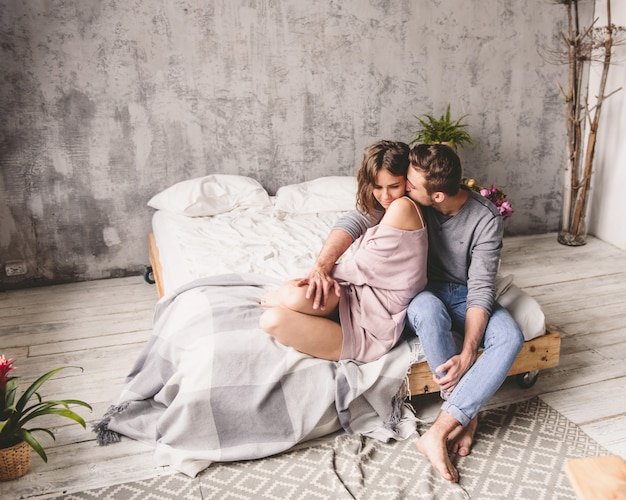 Молодой битник с бородой и привлекательной женщиной, отдыхая дома, сидя на кровати у себя дома