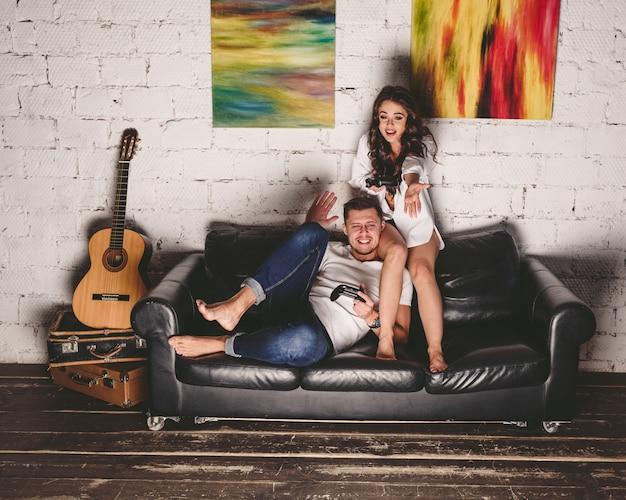 幸せなカップルのコンソールでビデオゲームをプレイし、楽しんで