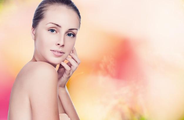 美しい女性が肌の顔を気遣うこと - 白で隔離されるスタジオでポーズをとる