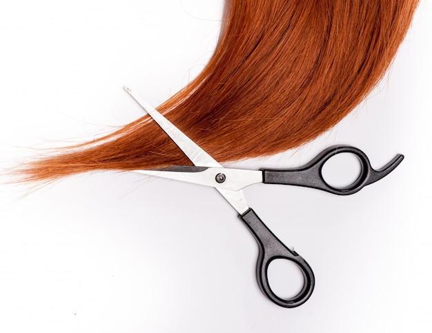 光沢のある赤い髪と白で隔離される髪を切る鋏