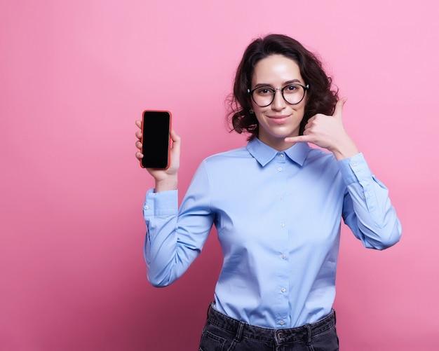 孤立したまま携帯電話を使用して夏服のかなり微笑の女の子の肖像画