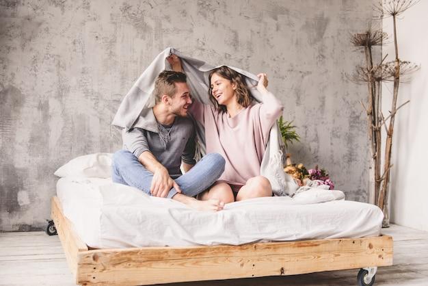 ロマンチックな幸せな若いカップルは屋内の現代家の階段でリラックスします。