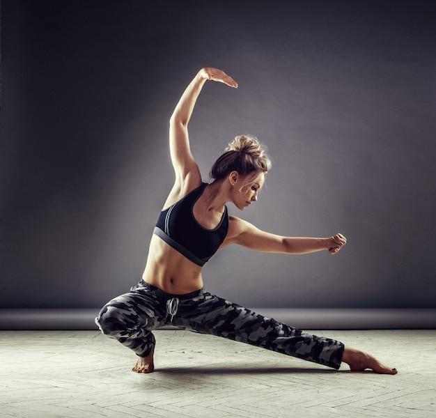 スポーツウェアの壁の背景に高いジャンプで若いスリムな女性ダンサー