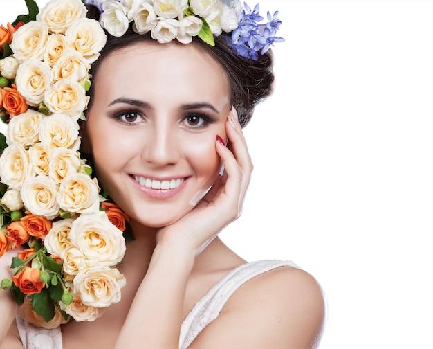 白いスタジオ撮影に分離されたバラと魅力的な笑顔の女性の肖像画