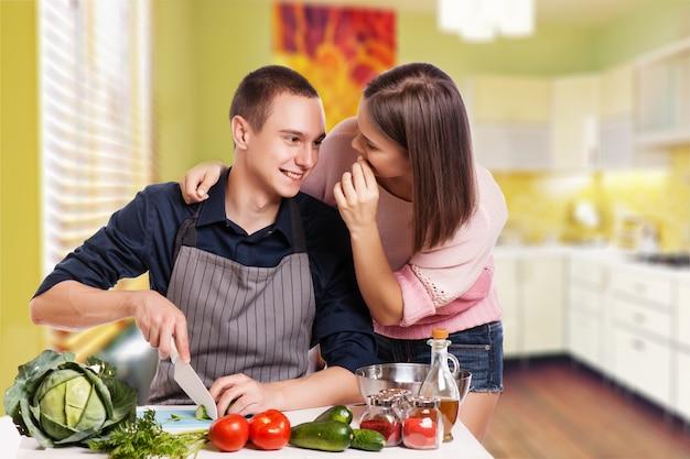 幸せな若いカップルは、モダンなキッチンで楽しい時を過す