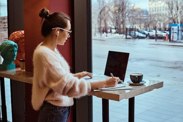Женщина-предприниматель работает из кафе и разговаривает по мобильному телефону с наушниками