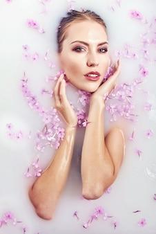 Девушка модели красоты курорта купая в ванне молока, спе и концепции заботы кожи.