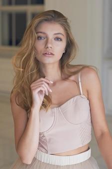 Красивая женщина модель позирует в элегантном платье в студии.