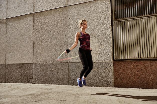 市壁に対してスキップする若いフィットネス女性ロープ。