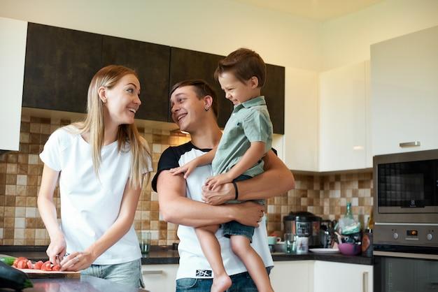 幸せな家族が自宅の台所で野菜を一緒に準備します。