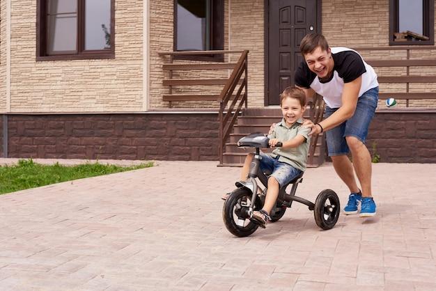 Счастье отец и сын на велосипеде на открытом воздухе