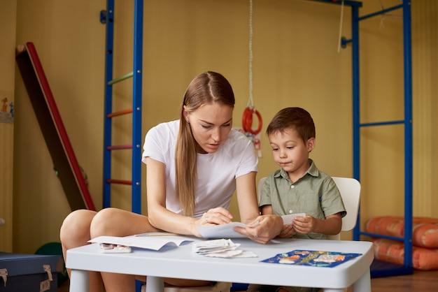 Мать и сын рисуют за столом в комнате.