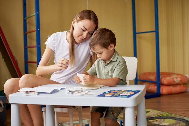 母と息子は部屋の中のテーブルで絵を描きます。
