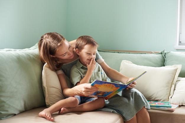 若い母親、彼女の子供に本を読んで、彼らの家のリビングルームで少年、窓から太陽の光