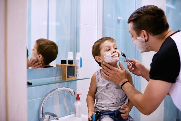 Мужчина и маленький мальчик с пеной для бритья на лицах смотрит в зеркало в ванной и смеется. отец и сын с удовольствием во время бритья в ванной комнате.