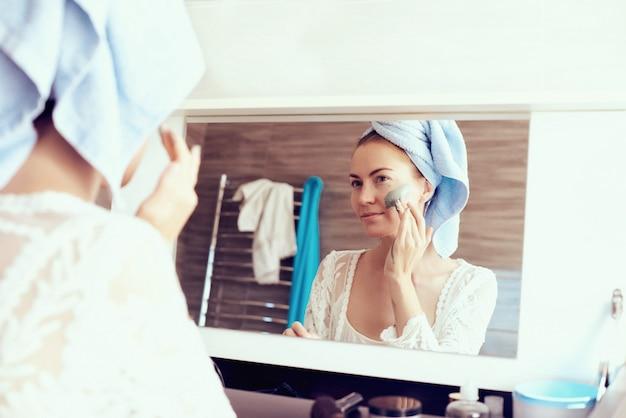 Молодая милая женщина в халате и с полотенцем на голове извлекая лицевую маску перед зеркалом в ванной комнате. уход за кожей и концепция красоты