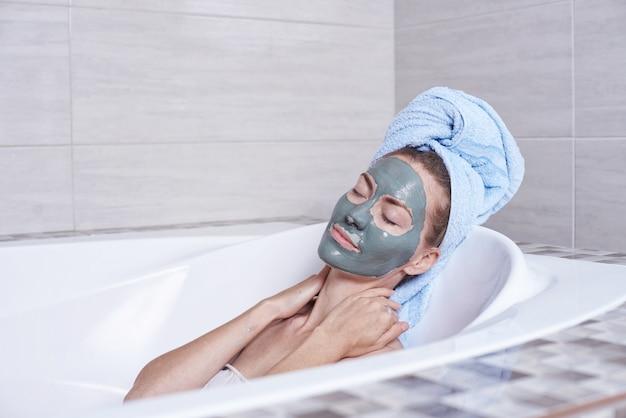 Портрет женщины в альгинатной маске для лица, лежащей в ретро ванне в ванной комнате