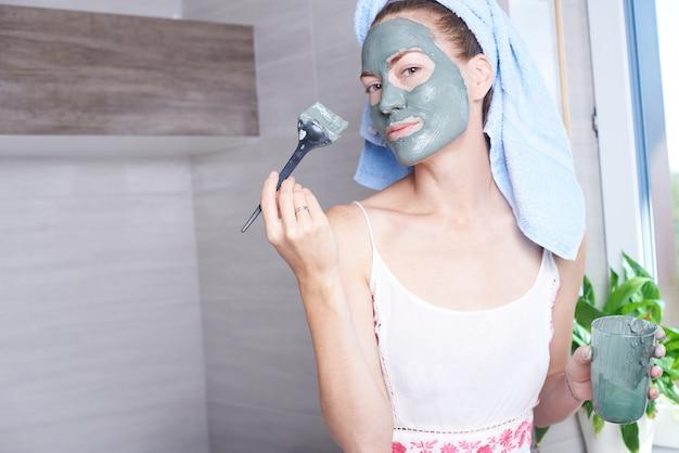 バスルームの鏡で見ている顔に保湿スキンクリームを適用する女性。彼女の顔色層保湿剤の世話をする少女。スキンケアスパトリートメント。