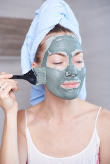 Женщина, применяя маску увлажняющий крем для кожи на лице, глядя в зеркало в ванной. девушка ухаживает за своим цветом лица увлажняющий крем. курортное лечение по уходу за кожей.