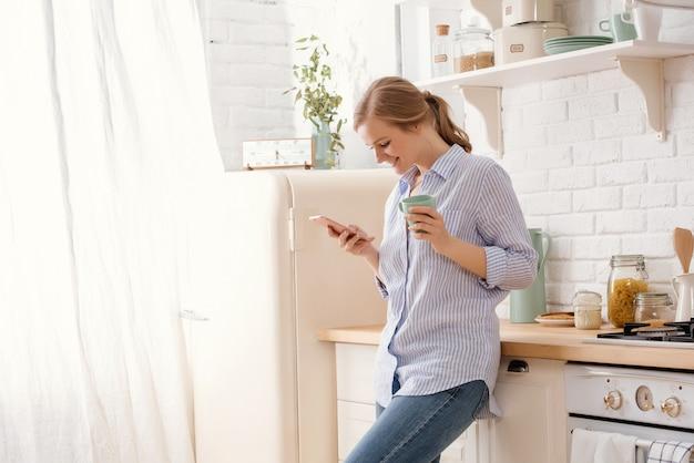 コーヒーマグカップと近代的な家の主催者の台所のテーブルにもたれてスマートフォンを使用して若い女性。電話のメッセージを読んで笑顔の女性。テキストメッセージを入力して幸せなブルネットの少女。