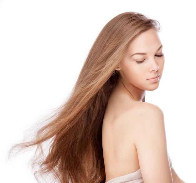 美しい長い茶色の空飛ぶ毛を持つ官能的な若い女性