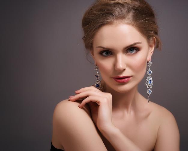 Белокурая женщина с вьющимися красивыми волосами, улыбаясь на сером фоне.
